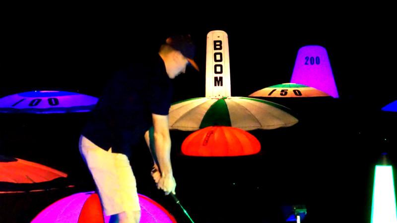 night golfer hitting at interactive range